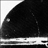 This original 1930 cloud-chamber photograph by Carl Anderson shows the track of a positively charged particle (thin track curving to the left) of electronic mass slowed down by passing upward through a lead plate (horizontal thick line).